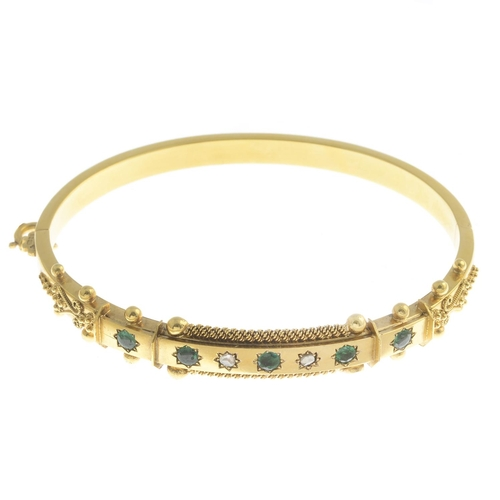 38 - A late Victorian gold emerald and diamond hinged bangle. Estimated dimensions of one emerald 3 by 3m...