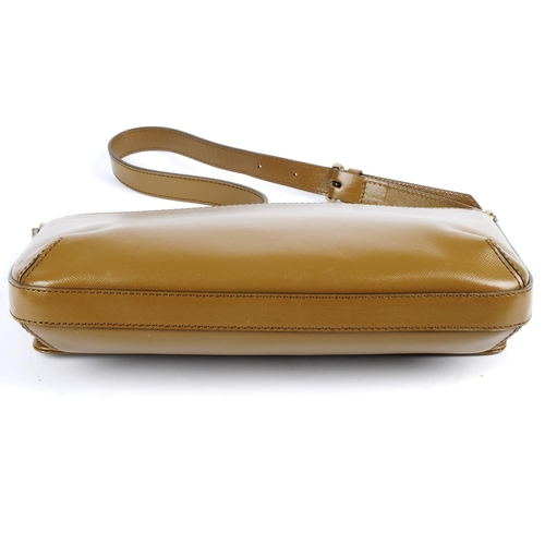 26 - BURBERRY - a leather handbag. Designed with a brown glossy leather exterior, with a rear slip pocket...