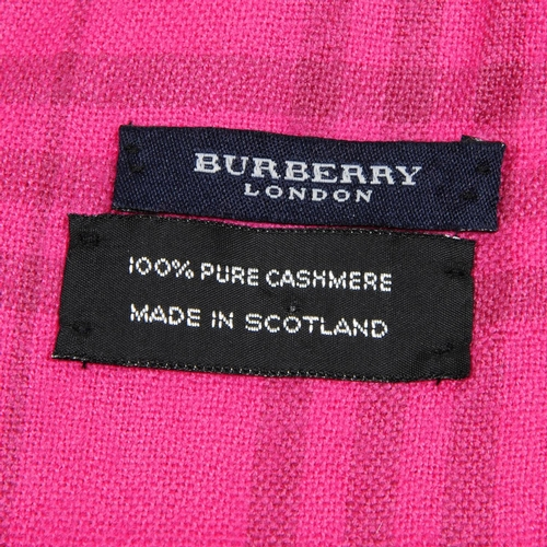 29 - BURBERRY - a fuchsia pink cashmere shawl. Featuring a pale brown check pattern throughout and two fr...