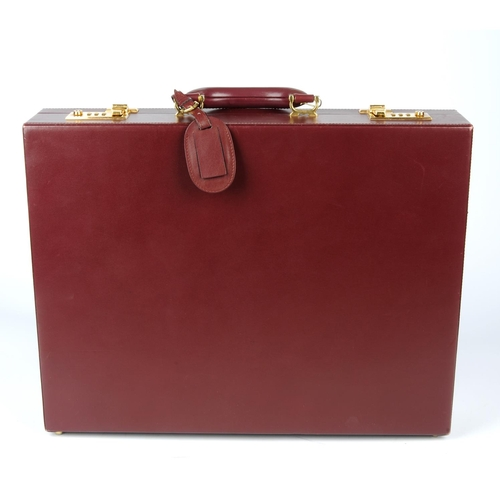 41 - CARTIER - a Must De Cartier Bordeaux leather briefcase. Designed with a structured shape, with maker...