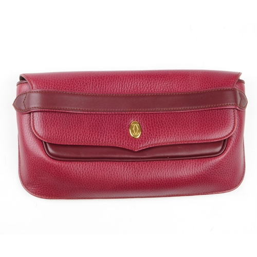 47 - CARTIER - a Bordeaux leather clutch and a pair of leather gloves. The clutch, crafted from two-tone ...