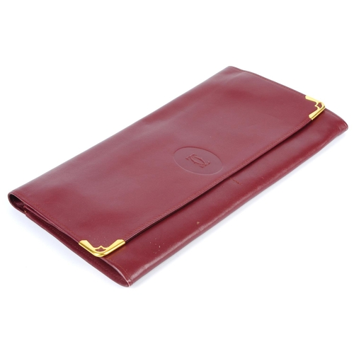48 - CARTIER - a Bordeaux leather travel wallet. Crafted from maker's signature burgundy leather, with fr...