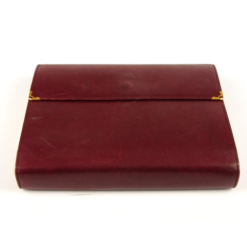 49 - CARTIER - a Bordeaux leather address book journal. Designed with a burgundy leather exterior cover, ...