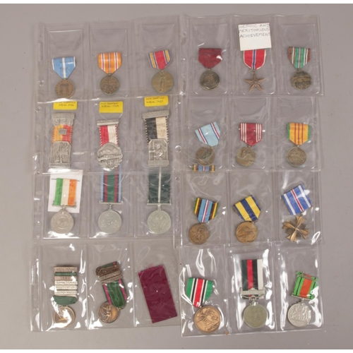 18 - A collection of twenty five medals and ribbons including Police, Swiss Shooting etc....