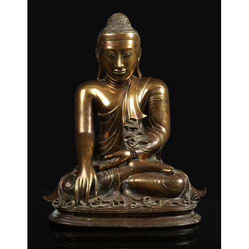 A large 17th century Sino-Tibetan bronze statue of Buddha Shakyamuni. With glass inset eyes and seated in meditation on a simple reeded plinth, 52cm.