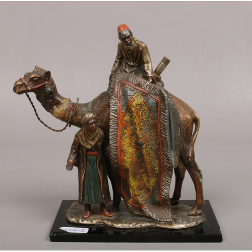 After Franz Bergman, a cold painted Spelter table lighter formed as a camel and two rug sellers.