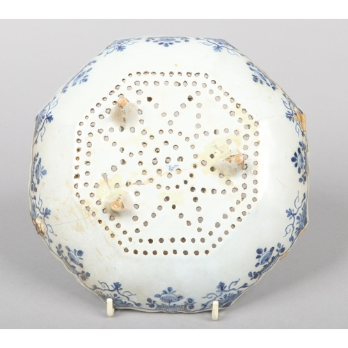49 - A 19th century Dutch delft blue and white cress drainer of scalloped octagonal form. Painted with ch...