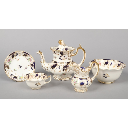 30 - A Rockingham part tea service with single spur handles. Moulded with scrolling foliage, having wet b...