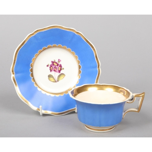 37 - A Rockingham teacup and saucer with square handle, gilded, having blue grounds and painted with flow...