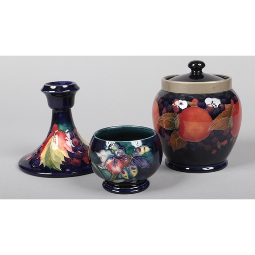 57 - Three pieces of Moorcroft pottery. A biscuit jar and cover with pewter mount and decorated in the po...