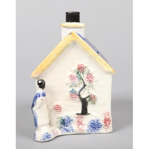 60 - An early 19th century prattware money box, probably South Yorkshire. Formed as a cottage flanked by ...