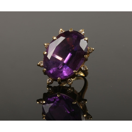 An 18ct gold amethyst and diamond cocktail ring. With a large faceted ovoid amethyst 25mm x 18mm, with eight round cut diamonds in a starburst setting, 17 grams gross, size R.