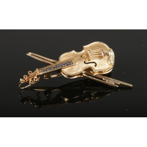 A 9ct gold, diamond and sapphire brooch, formed as a violin. 4.69g.