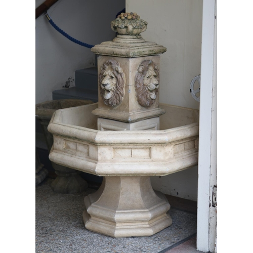 A large composition stone garden fountain. Octagonal in form and ornamented with four lion masks, 126cm high.