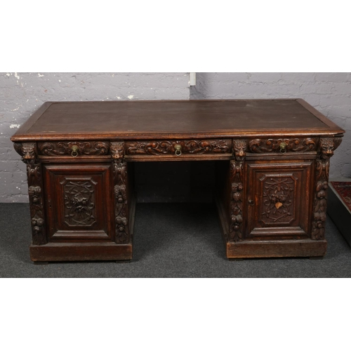 A large and impressive Victorian Gothic revival heavily carved oak partners desk with carved lion mask corbels, 103 x 175cm.