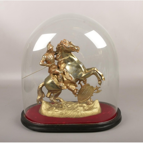 42 - A gilt metal figure of a knight on horseback, under Victorian glass dome....