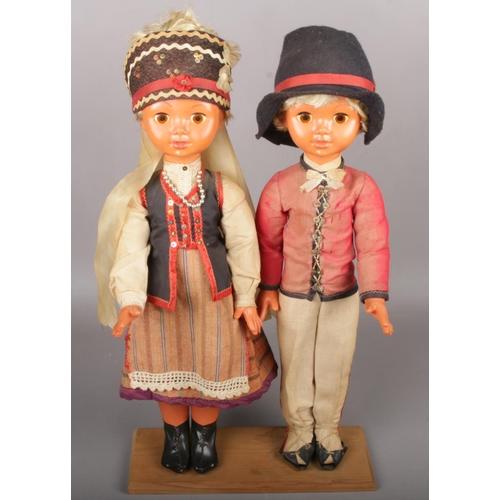 14 - A pair of European dolls raised on wooden plinth....