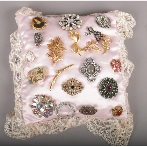 19 - A quantity of costume brooches to include colour and white paste examples....