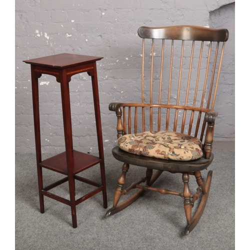 549 - A spindle back rocking arm chair along with a mahogany two tier jardinière stand....