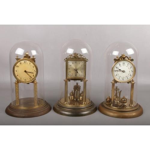 86 - Three German brass torsion clocks under glass domes. Two marked for Jahresuhrenfabrik the other for ...