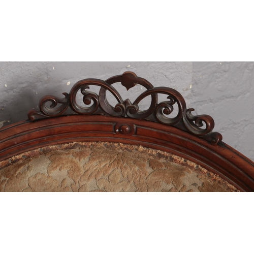 603 - A Victorian carved walnut upholstered tub chair. With open scroll work cresting rail and raised on r...