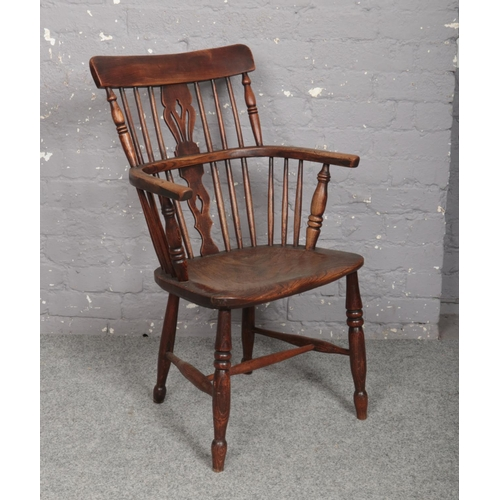 604 - A 19th century ash and elm comb back Windsor elbow chair in the Thames valley tradition....
