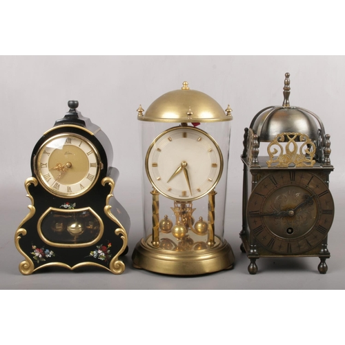 123 - A German brass torsion clock in glass case, A Kern tosion clock in ebonized French style case and a ...