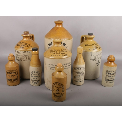 57 - A collection of stoneware flagons and bottles, mostly Sheffield advertising examples....