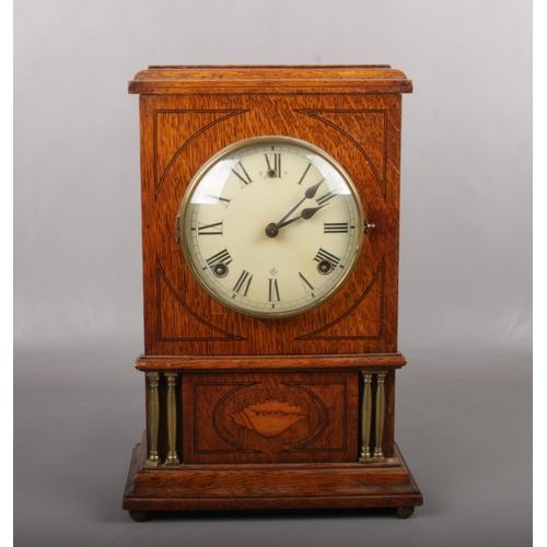 97 - An American oak cased 8 day mantel clock. With brass column supports and marquetry shell patera. Hav...