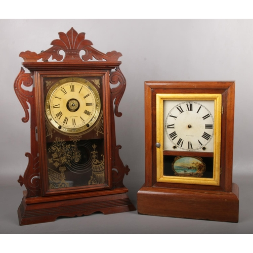 103 - A 19th century mahogany cased gingerbread tin tang alarm clock by Seth Thomas along with another clo...