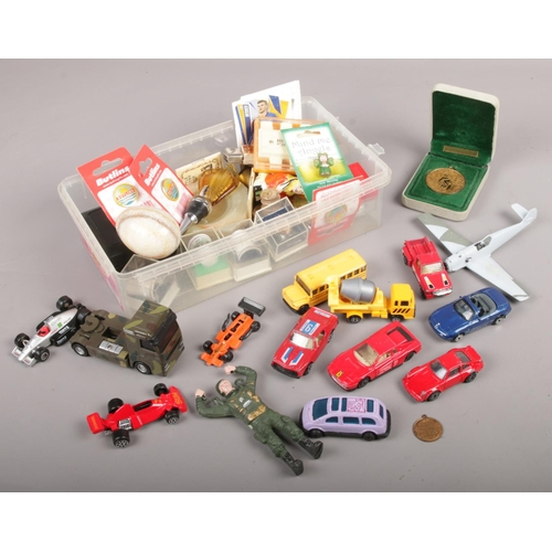107 - A box of collectables, to include Butlins badges, medals, model vehicles etc....