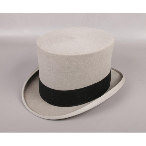 140 - A gentleman's grey felt top hat with black band. Label for Moss Bros, Covent Garden. Size 7 1/4....