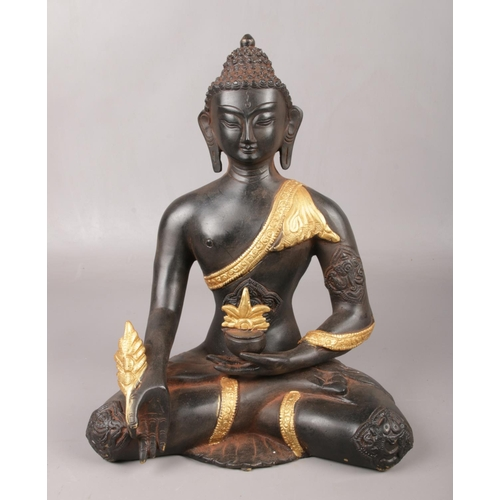 180 - A parcel gilt cast bronze figure of a medicine Buddha. (Height 29cm)....