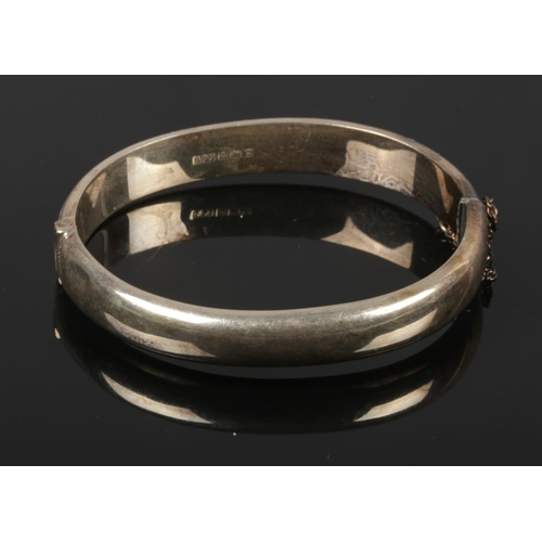 421 - A silver bangle with engraving detailing....