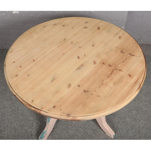 582 - A pine centre pedestal circular kitchen table. With distressed painted base and striped top, 106cm d...