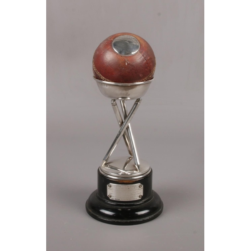 A George V silver cricket trophy. Formed from a Gunn & Moore  cricket ball with silver plaque inscribed H. Bolton, Helensburgh C. C. v Milngavie & Bearsden C. C. 10th June 1922, 10 wickets for 10 runs, raised on a tripod of silver cricket stumps over and ebonized plinth with plaque, further inscribed, with this ball... Assayed Birmingham 1924, 21.5cm.