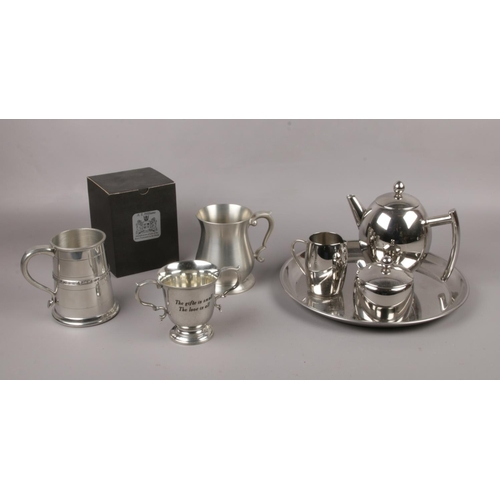12 - A stainless steel teapot, sugar bowl, milk jug, serving tray to include two pewter tankards and AE W...