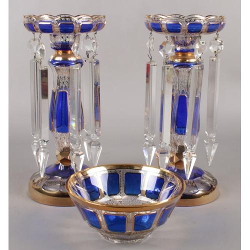 A pair of clear glass lustres, with Bristol blue panels and gilt decoration, along with matching bowl. (Height 28cm, Diameter of bowl 15.5cm).