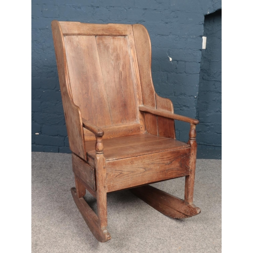 An 18th century elm rocking lambing chair with single drawer.