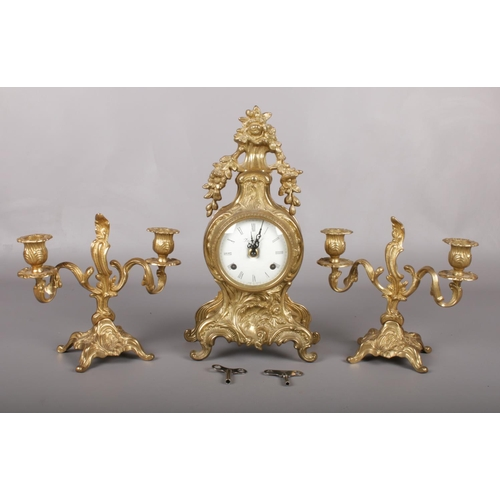Italian cartouche shaped gilt metal clock garniture. The white enamel dial signed 'Imperial' with roman numerals houses a twin train 'Franz Hermle' movement striking the hours and halves on two bells. H:33cm