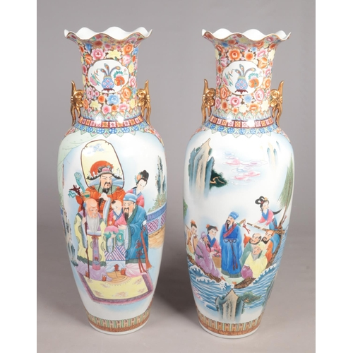 25 - A pair of very large decorative oriental floor standing vases. Decorated with landscapes and figures...
