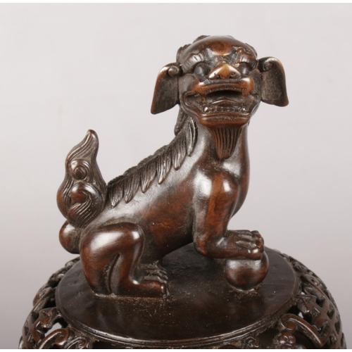 26 - A large Chinese lidded bronze censor. Surmounted with a temple lion. Character marks to the base. 37...