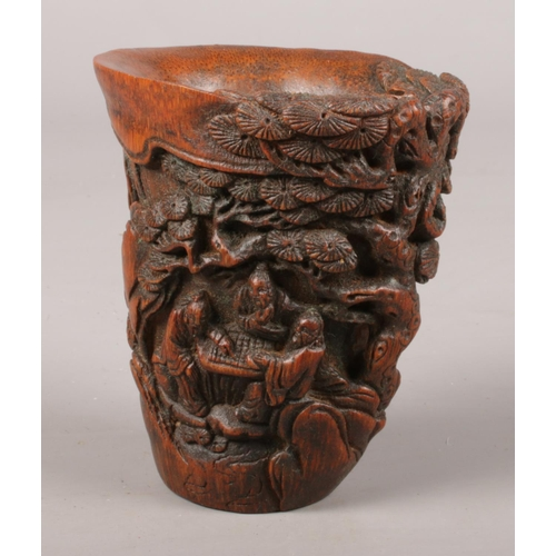 29 - A Chinese carved bamboo libation cup. Decorated with trees and figures.