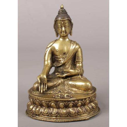 30 - A 19th century Sino Tibetan bronze small devotional statue of a seated Buddha with phurba and raised...