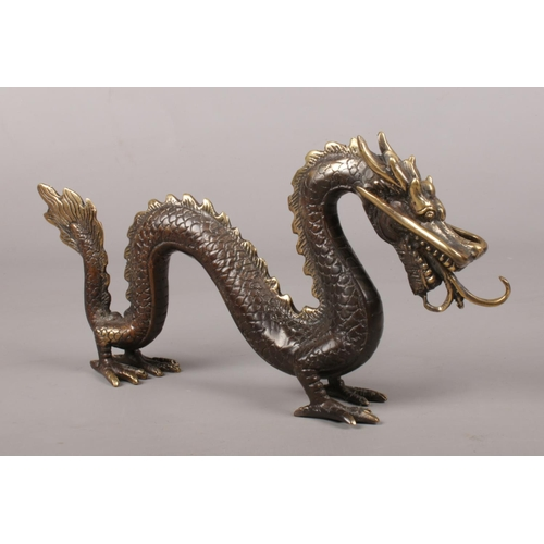 31 - A bronze Chinese dragon. Height 13cm, Length 26cm.