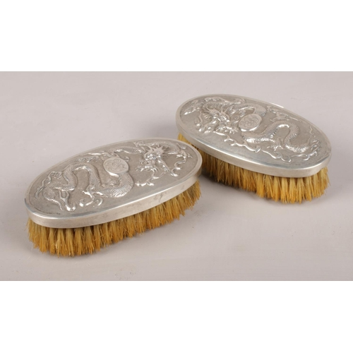 32 - A pair of Chinese clothes brushes with silver mounted tops. Decorated with dragons.