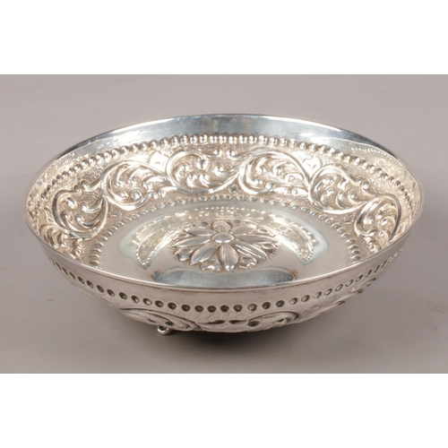 38 - A silver bowl with repousse decoration and central floral design. Raised on three supports. Stamped ...