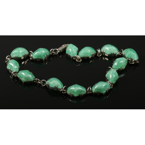 57 - A silver and green paste Riviere necklace. Claw set with box clasp. Possibly Czechoslovakian Peking ...