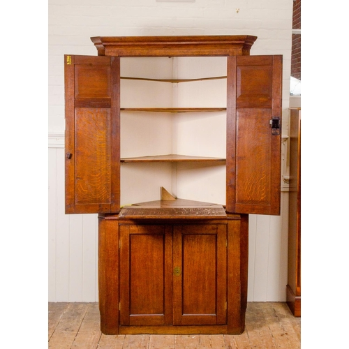 18 - An early Victorian oak cross banded double door corner cupboard, with fitted interior, width 109cm...