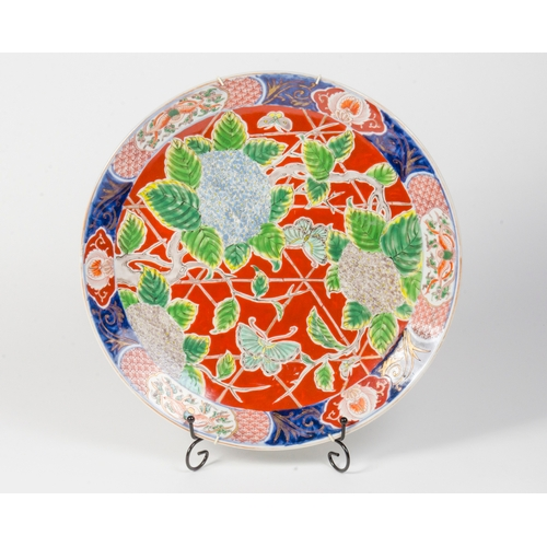 191 - A Japanese Imari Charger, decorated with Chrysanthemums and Butterflies, on a bamboo and red decorat...